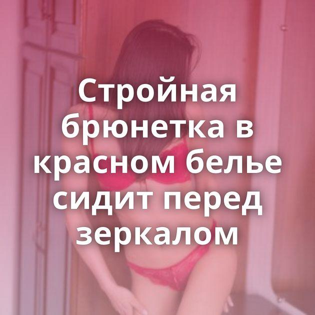 Стройная брюнетка в красном белье сидит перед зеркалом