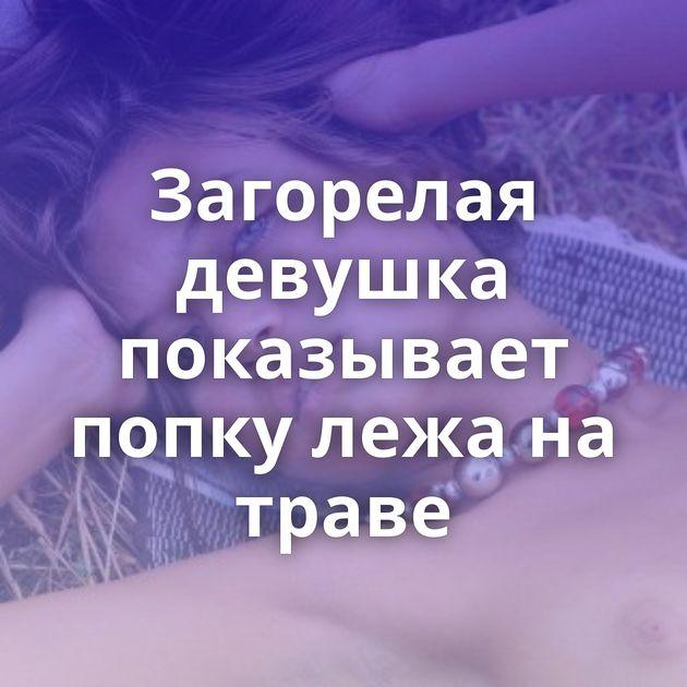 Загорелая девушка показывает попку лежа на траве