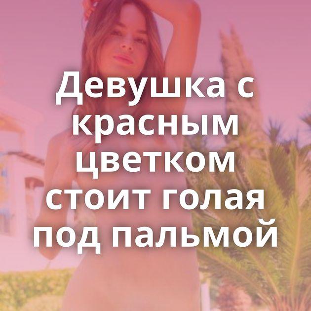 Девушка с красным цветком стоит голая под пальмой