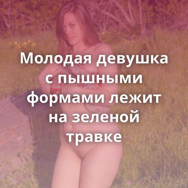 Молодая девушка с пышными формами лежит на зеленой травке