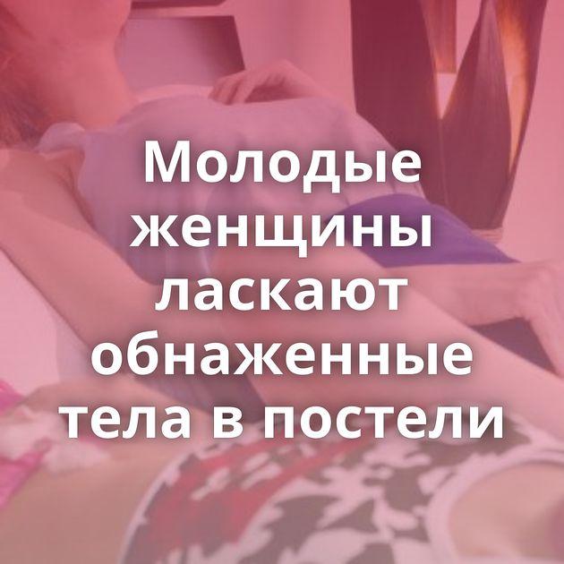 Молодые женщины ласкают обнаженные тела в постели
