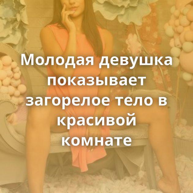 Молодая девушка показывает загорелое тело в красивой комнате