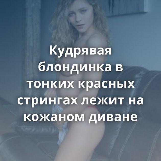 Кудрявая блондинка в тонких красных стрингах лежит на кожаном диване