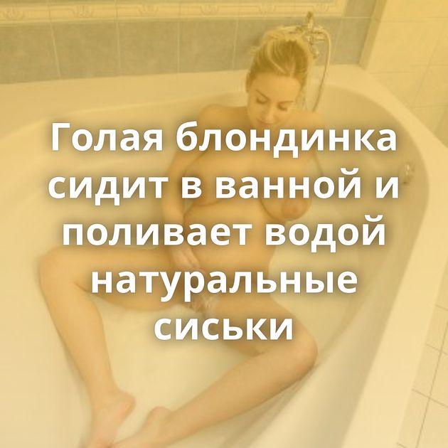 Голая блондинка сидит в ванной и поливает водой натуральные сиськи
