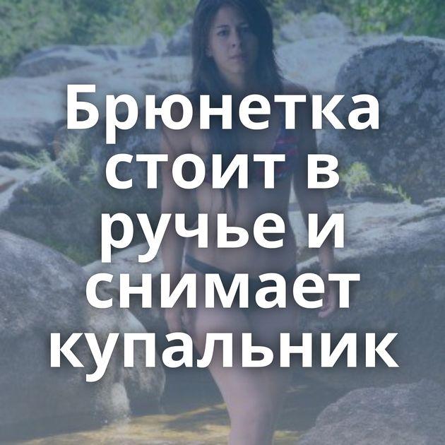 Брюнетка стоит в ручье и снимает купальник