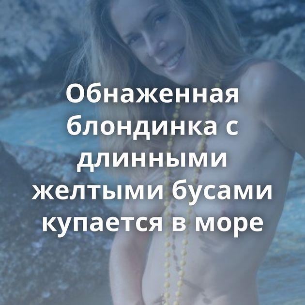 Обнаженная блондинка с длинными желтыми бусами купается в море
