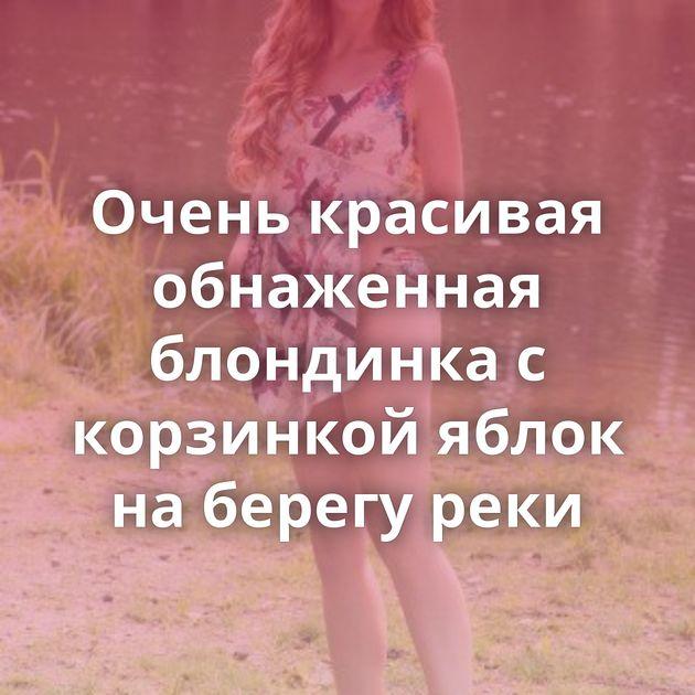 Очень красивая обнаженная блондинка с корзинкой яблок на берегу реки