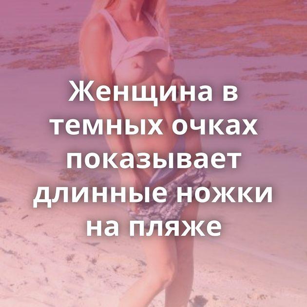 Женщина в темных очках показывает длинные ножки на пляже