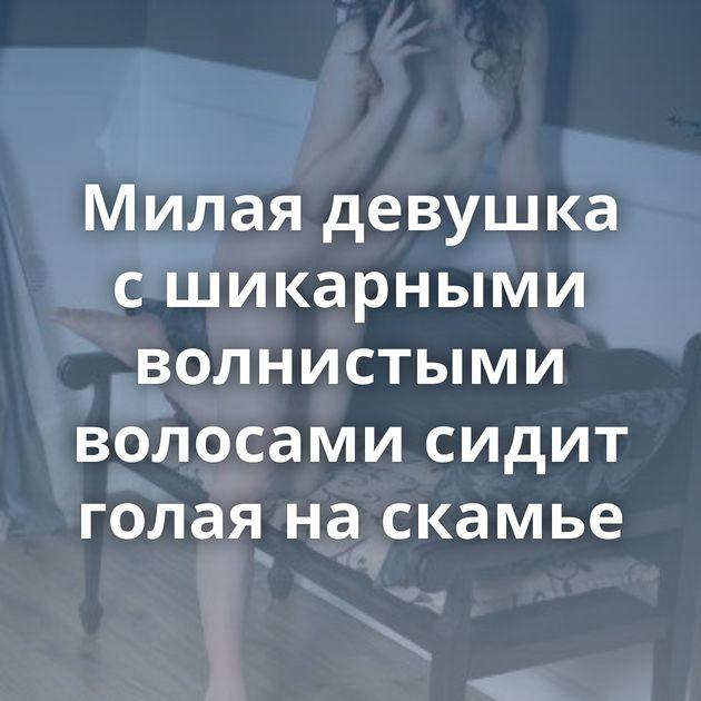 Милая девушка с шикарными волнистыми волосами сидит голая на скамье