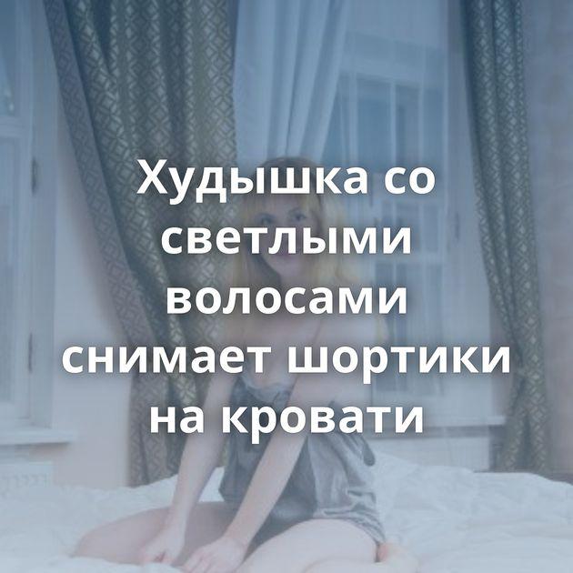 Худышка со светлыми волосами снимает шортики на кровати