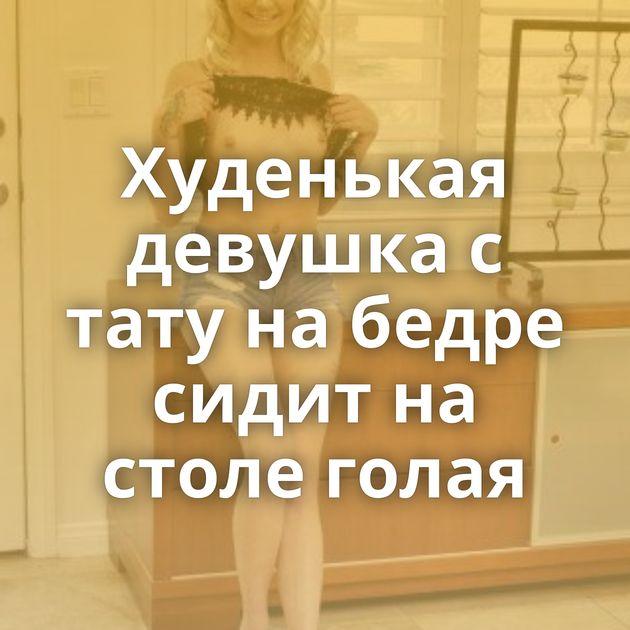 Худенькая девушка с тату на бедре сидит на столе голая