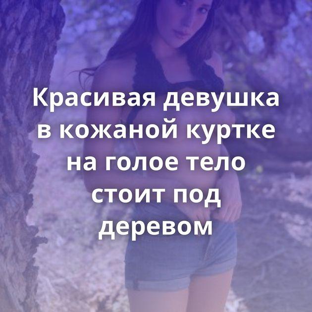 Красивая девушка в кожаной куртке на голое тело стоит под деревом