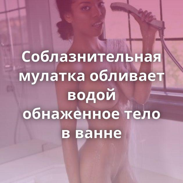 Соблазнительная мулатка обливает водой обнаженное тело в ванне