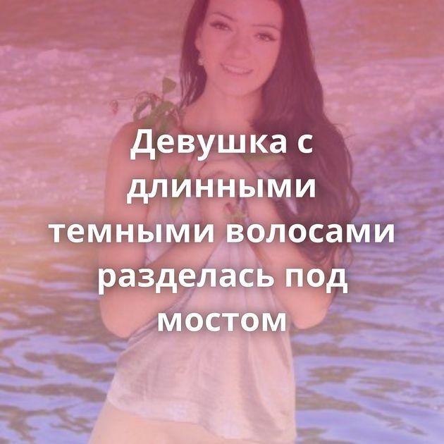 Девушка с длинными темными волосами разделась под мостом
