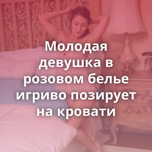 Молодая девушка в розовом белье игриво позирует на кровати