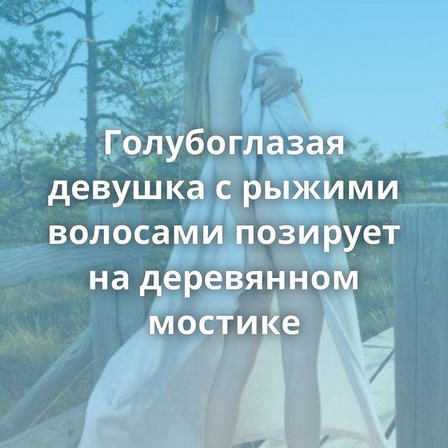 Голубоглазая девушка с рыжими волосами позирует на деревянном мостике