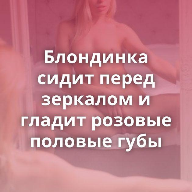 Блондинка сидит перед зеркалом и гладит розовые половые губы