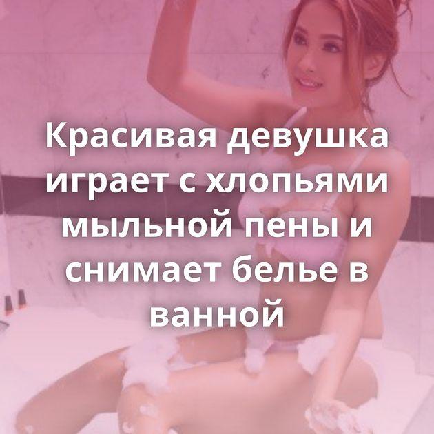 Красивая девушка играет с хлопьями мыльной пены и снимает белье в ванной