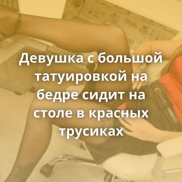 Девушка с большой татуировкой на бедре сидит на столе в красных трусиках