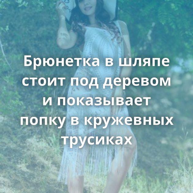 Брюнетка в шляпе стоит под деревом и показывает попку в кружевных трусиках