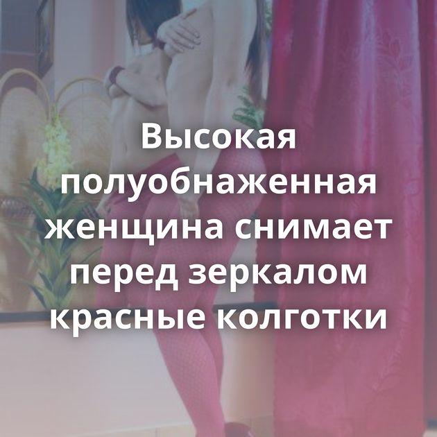 Высокая полуобнаженная женщина снимает перед зеркалом красные колготки