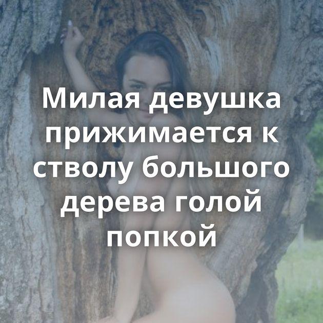 Милая девушка прижимается к стволу большого дерева голой попкой