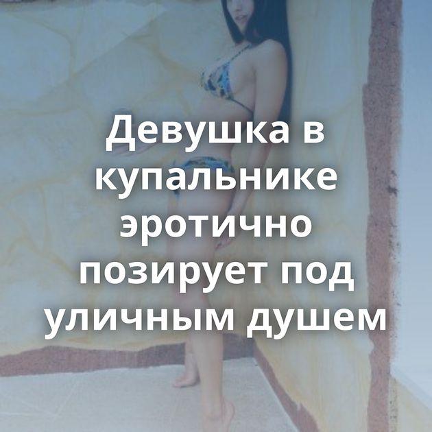 Девушка в купальнике эротично позирует под уличным душем