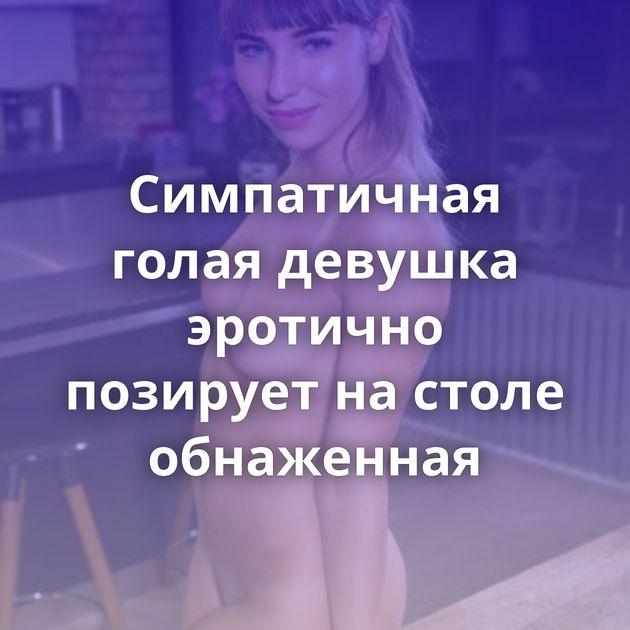 Симпатичная голая девушка эротично позирует на столе обнаженная