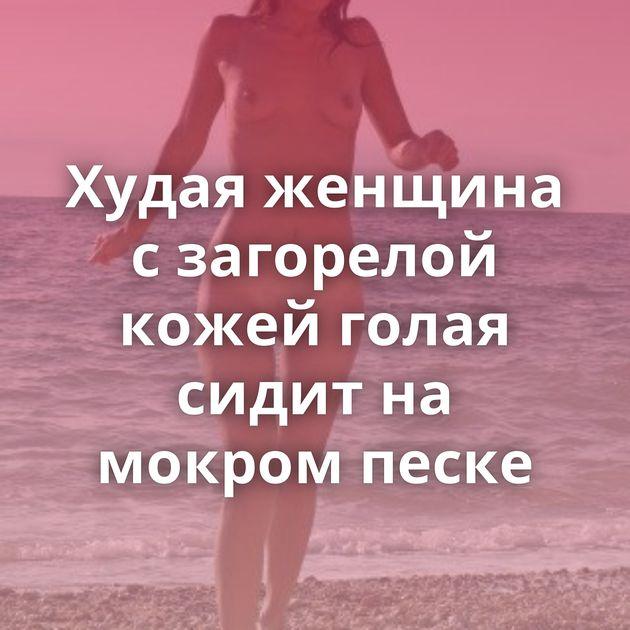 Худая женщина с загорелой кожей голая сидит на мокром песке