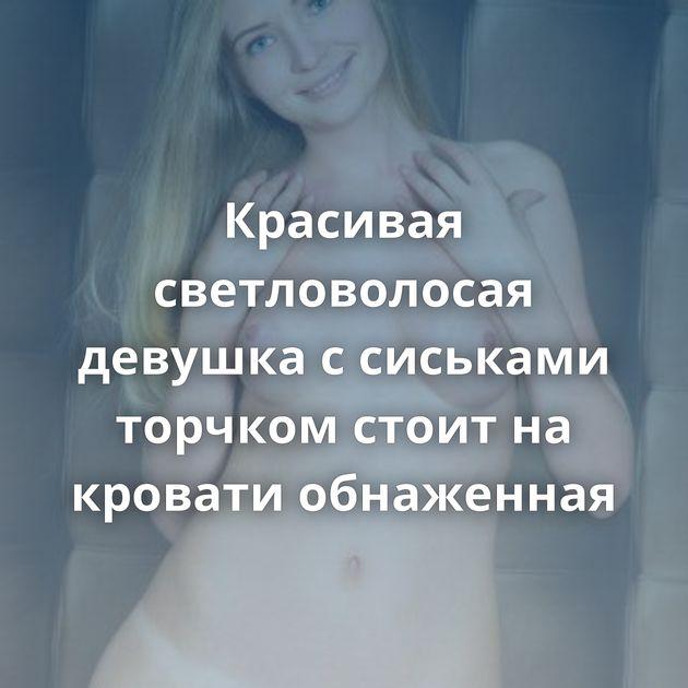 Красивая светловолосая девушка с сиськами торчком стоит на кровати обнаженная