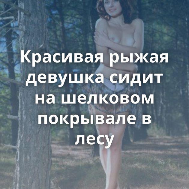 Красивая рыжая девушка сидит на шелковом покрывале в лесу