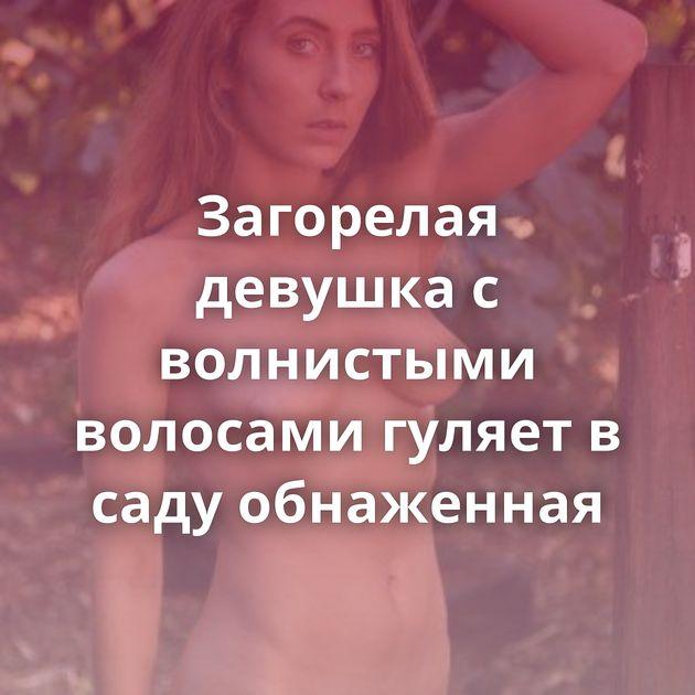 Загорелая девушка с волнистыми волосами гуляет в саду обнаженная