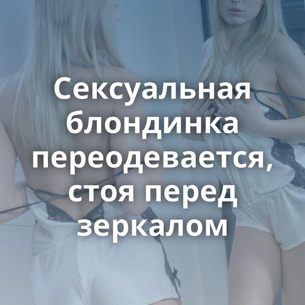 Сексуальная блондинка переодевается, стоя перед зеркалом