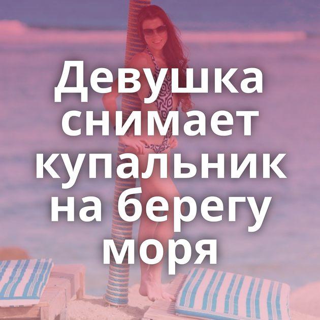 Девушка снимает купальник на берегу моря