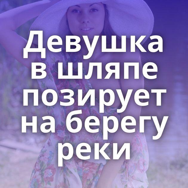 Девушка в шляпе позирует на берегу реки