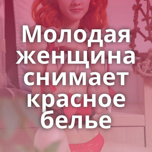 Молодая женщина снимает красное белье